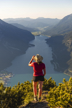 IBXMMW05086812 Young hiker, woman looking into the distance, view from B'renkopf mountain to Lake Achen, left Seebergspitze and Seekarspitze, right Rofan Mountains, Tyrol, Austria, Europe