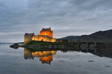 IBXOLF03729816 Eilean Donan Castle, ancestral seat of the Scottish clan of Macrae, reflected in Loch Duich in the evening, Dornie, Highlands, Scotland, United Kingdom, Europe