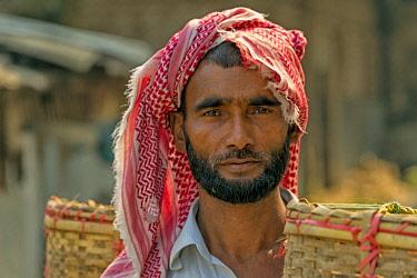 AS03KSU0308 Tribe man carrying basket, Chimbuk Hill, Bandarban, Chittagong Division, Bangladesh.