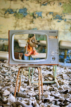 AS43EWI0250 Ukraine, Pripyat, Chernobyl. Gas masks, many of them child-sized, litter the floor of an abandoned school. One has been placed over a doll's head. Seen through an empty television screen.