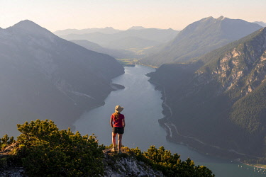 IBXMMW05091580 Young woman looking over mountain landscape, view from the mountain Barenkopf to Lake Achensee, left Seebergspitze and Seekarspitze, right Rofan Mountains, Tyrol, Austria, Europe