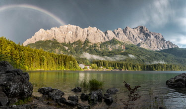 IBXMMW05092209 Rocks on the shore, Eibsee lake in front of Zugspitze massif with Zugspitze with rainbow, Wetterstein range, near Grainau, Upper Bavaria, Bavaria, Germany, Europe