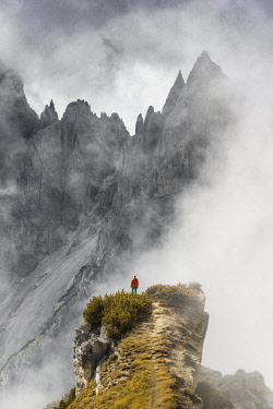 Mountaineer stands on a ridge, behind mountain peaks and pointed rocks, dramatic clouds, Cimon di Croda Liscia and Cadini Group, Auronzo di Cadore, Belluno, Italy, Europe