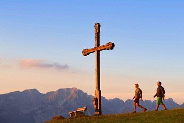 IBXNEX05053091 Hikers at the summit cross of the Kraftalm, in the background the Wilder Kaiser Mountains, Hohe Salve, Itter, Kitzbuhel Alps, Tyrol, Austria, Europe