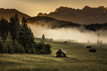 IBXSEI04539182 Small cabin on mountain meadow at forest edge, Geroldsee in the background Karwendel Mountains at sunrise, Kaltenbrunn, Upper Bavaria, Germany, Europe