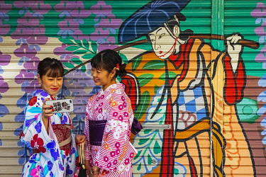 TPX72991 Japan, Honshu, Tokyo, Asakusa, Two Women in Kimono Taking Selfie Photos in front of Colourful Store Shutter Painting
