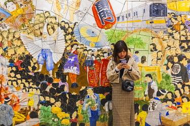 TPX73009 Japan, Honshu, Tokyo, Asakusa, Ginza Subway Line, Asakusa Station, Young Woman Standing in Front of Mosaic depicting Popular Festivals