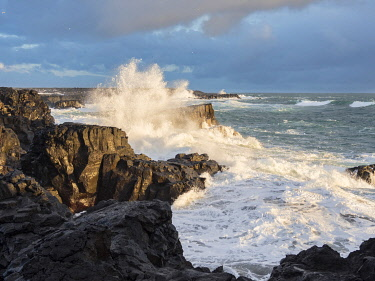 EU14MZW1775 Coastline at Brimketill during winter storm conditions at sunset. Reykjanes Peninsula, Iceland.