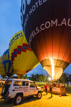 AUS4085AW Tourits reading for balloon flight whilst filling hot air balloon. Canberra, Greater Canberra, Australian Capital Territory, Australia