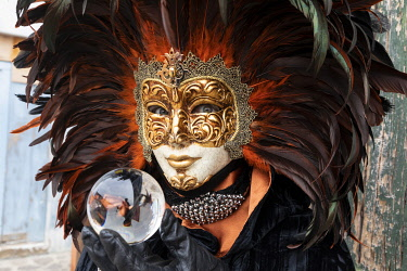 ITA15136AW A woman in a feather Venetian mask poses with a glass ball during the Venice Carnival, Burano, Venice, Venato, Italy