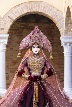 ITA15138AW A woman wearing an Indian style costume and mask poses in the cloisters of Chiesa di San Francesco della Vigna, Venice, Veneto, Italy