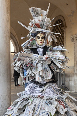 ITA15140AW A woman covered in newspaper walks through St. Mark's square dring the Venice Carnival, Venice; Veneto; Italy