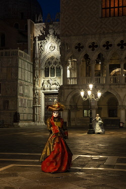 ITA15150AW A woman in costume poses in St. Mark's square during the Venice Carnival, Venice, Veneto, Italy