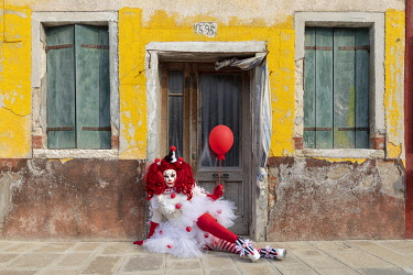 ITA15162AW A woman dressed as a clown holds a ballon in front of a colourful facade on Burano, Venice, Venato, Italy