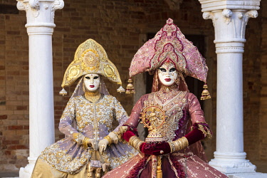 ITA15163AW Two women wearing Indian style costumes and masks pose in the cloisters of Chiesa di San Francesco della Vigna, Venice, Veneto, Italy