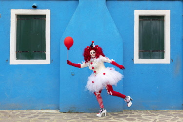 ITA15174AW A woman dressed as a clown holds a ballon in front of a colourful facade on Burano, Venice, Venato, Italy
