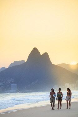 BRA3848AW South America, Brazil, Rio de Janeiro. A group of friends walk along the sand on Ipanama / Leblon beach as the sun sets behind Dois Irmaos peak