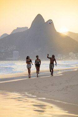 BRA3849AW South America, Brazil, Rio de Janeiro. A group of friends walk along the sand on Ipanama / Leblon beach as the sun sets behind Dois Irmaos peak