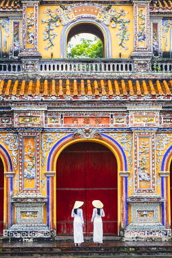 VIT1778AW Southeast Asia, Vietnam, Hue. Two young women wearing Ao Dai dresses stand next to an elaborately carved gateway to the Purple Citadel in the historical imperial old city and UNESCO world heritage sit...