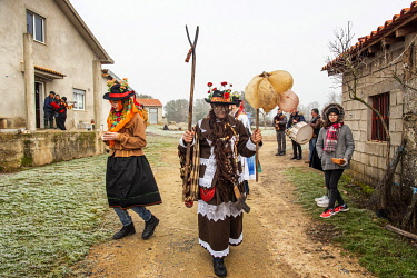 POR10884AW The three main characters of the Winter Solstice Festivities at Vila Ch�A? de Braciosa dance in front of the house owner that made offerings for the Communal Supper. Miranda do Douro, Portugal