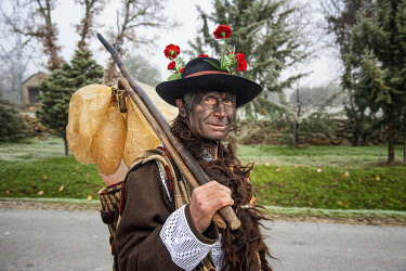 POR10892AW At the Winter Solstice Festivities in Vila Ch�A? de Braciosa, the Velha character (the Old Woman) is painted black and carries a stick with several pork bladders. Miranda do Douro, Trás-os-Montes. Po...