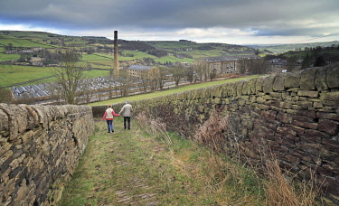 ENG16596AW England, West Yorkshire, Halifax. Couple walking down a steep path towards the mills of Luddenden.