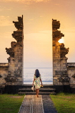 IDA1109AW Indonesia, Bali, Candidasa. A young woman walking through the doorway of a traditional Balinese temple overlooking the Pacific ocean MR