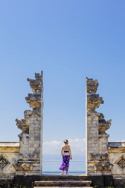 IDA1119AW Indonesia, Bali, Candidasa. A local young woman standing in the gateway to the Pura Candidasa temple, and wearing traditional busana adat temple clothes - comprising a white kebaya blouse, a sash and...