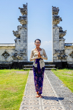 IDA1120AW Indonesia, Bali, Candidasa. A local young woman standing in the gateway to the Pura Candidasa temple, and wearing traditional busana adat temple clothes - comprising a white kebaya blouse, a sash and...