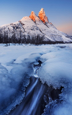 NOR1192AW Frozen river and Mt. Otertinden taking the first lights of the day, Tromso region, Norway