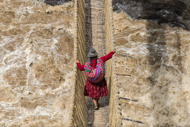 SA17KSU0094 Quechua woman crossing Queshuachaca (Q'eswachaka) rope bridge, one of the last standing Incan handwoven bridges, Quehue, Canas Province, Peru