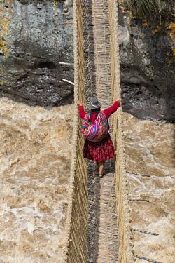 SA17KSU0119 Quechua woman crossing Queshuachaca (Q'eswachaka) rope bridge, one of the last standing Incan hand-woven bridges, Quehue, Canas Province, Peru.