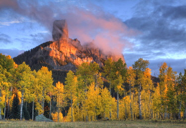 US06BJY1582 USA, Colorado, San Juan Mountains. Chimney Rock formation and aspens at sunset