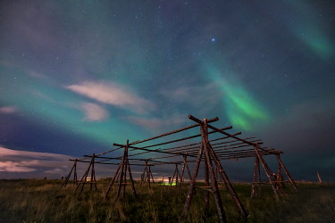 ICE42365AW Low angle view Aurora borealis over wooden stands for fish drying at night, Reykjavik, Iceland