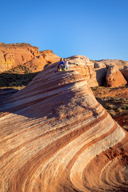 USA15360AW A couple sitting on top of Fire Wave rock formation before sunset, Valley of Fire State Park, Nevada, Western United States, USA