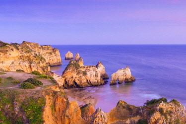 POR10946AWRF Portugal, Algarve, Alvor, Prainha, rock formations at dusk