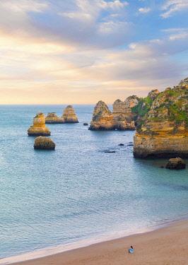 POR10927AW Portugal, Algarve,Lagos; Praia da Dona Ana, woman sitting on beach (MR)