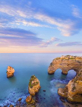POR10928AW Portugal, Algarve, Caramujeira, Praia de Marinha, double sea arch and coastal rock formations