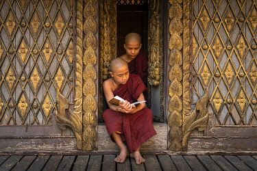 MYA2505AW Two novice monks reading a book at a monastery, Mandalay, Mandalay District, Mandalay Region, Myanmar