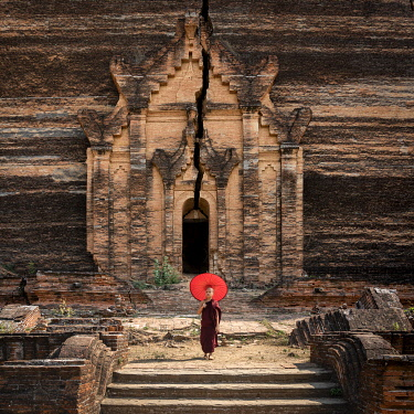 MYA2513AW Novice monk standing in front of the unfinished Pahtodawgyi pagoda known for a crack caused by a earthquake in 1839, Mingun, Mandalay, Sagaing Township, Sagaing District, Sagaing Region, Myanmar