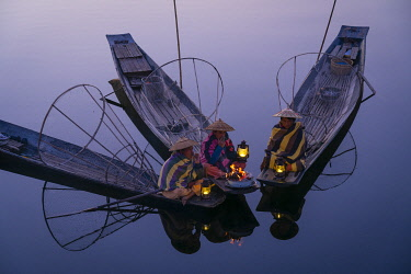 MYA2528AW Three fishermen sitting on their boats warming up around a fire before sunrise, Lake Inle, Nyaungshwe Township, Taunggyi District, Shan State, Myanmar