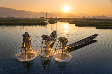 Three fishermen catching fish from boats using traditional conical nets at sunrise, Floating Gardens, Lake Inle, Nyaungshwe Township, Taunggyi District, Shan State, Myanmar