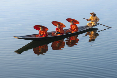 MYA2537AW Three monks in orange robes with bowls for alms giving and a leg-rowing fisherman commute using a boat across Lake Inle, Nyaungshwe Township, Taunggyi District, Shan State, Myanmar
