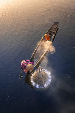MYA2538AW Elevated view of fisherman catching fish from boat using traditional conical net at sunrise on misty morning, Floating Gardens, Lake Inle, Nyaungshwe Township, Taunggyi District, Shan State, Myanmar