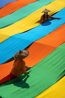 MYA2563AW Elevated view of two women hanging long pieces of dyed fabric to dry, Lake Inle, Nyaungshwe Township, Taunggyi District, Shan State, Myanmar
