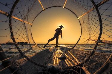 MYA2571AW Traditional leg-rowing fisherman viewed through conical fishing net rowing a boat on Lake Inle before sunset, Lake Inle, Nyaungshwe Township, Taunggyi District, Shan State, Myanmar