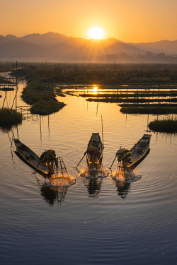 MYA2598AWRF Three fishermen catching fish from boats using traditional conical nets at sunrise, Floating Gardens, Lake Inle, Nyaungshwe Township, Taunggyi District, Shan State, Myanmar