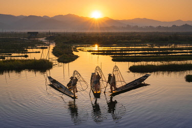 MYA2600AWRF Three fishermen catching fish from boats using traditional conical nets at sunrise, Floating Gardens, Lake Inle, Nyaungshwe Township, Taunggyi District, Shan State, Myanmar