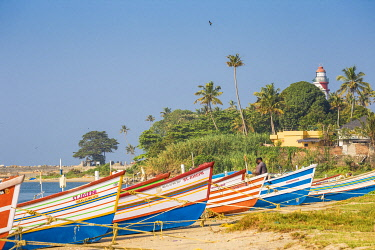 IN04412 India, Kerala, Kollam, Fishing boats on beach with Tangasseri Lighthouse in background