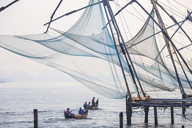 IN04495 India, Kerala, Cochin - Kochi, Fort Kochi, Fishermen in dug out canoes pass under Chinese fishing nets